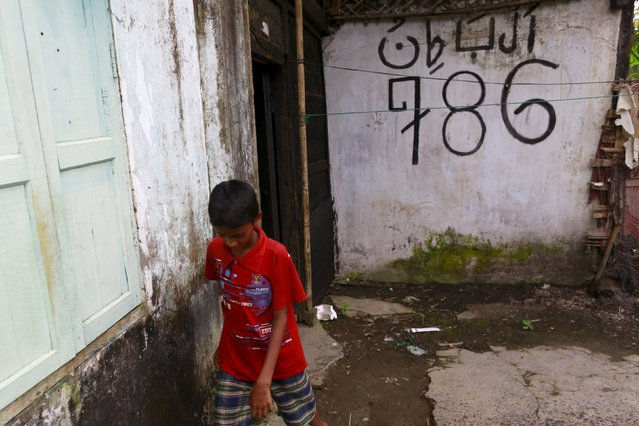 A boy walks past an abandoned hostel for students at the Aung Minglar quarter in Sittwe October 29, 2015. (Photo by Soe Zeya Tun/Reuters)