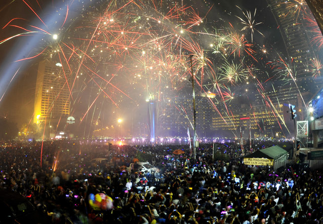 Thousand people watch fireworks at Hotel Indonesia roundabout in Jakarta during new year eve celebration, on January 1, 2015. (Photo by Andika Wahyu/Antara Foto)