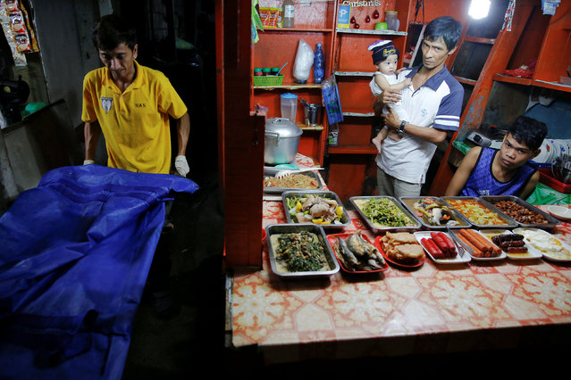 A food vendor holds a baby as funeral workers carry the body of one of two men killed inside a slum in port area on Manila, Philippines early October 21, 2016. (Photo by Damir Sagolj/Reuters)