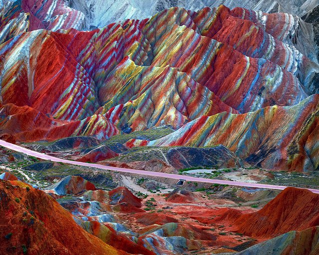 """There is no need to roll out the red carpet at Daxia in China's Gansu Province. The jaw-dropping rocky landscape is naturally red from a build-up of sandstone over many millions of years, while the rainbow effect comes from colourful mineral deposits. Sandstone and red mineral deposits were compressed into multi-coloured layers of rock. Movement of the giant plates that form Earth's crust pushed, cut, and folded the layers. The name Danxia means """"rosy clouds"""" in Chinese. (Photo by Imaginechina/Corbis)"""