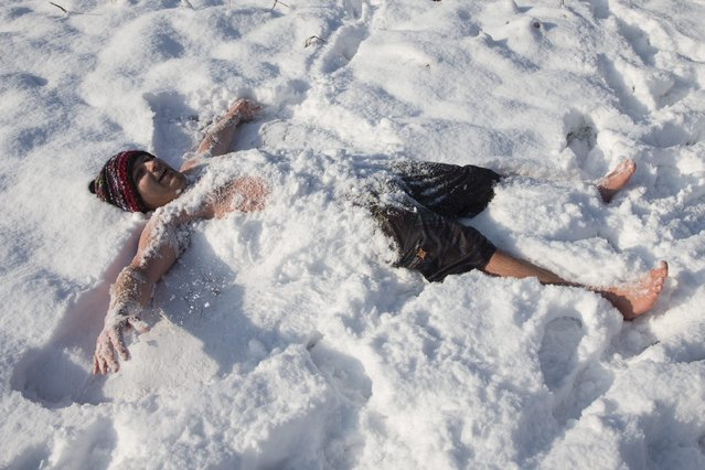 A participant frolics in the snow after taking part in the traditional New Year's swimming in the the Moossee lake with a water temperature of three degrees in Moosseedorf near Bern, Switzerland, 31 December 2014. (Photo by Peter Klaunzer/EPA)