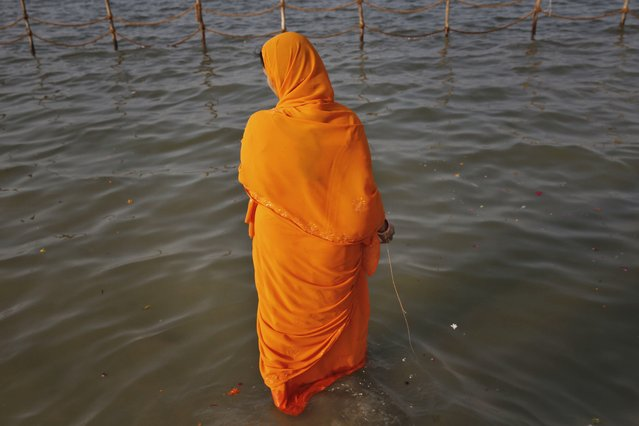 "An Indian Hindu devotee walks to take a holy dip at ""Sangam"", the confluence of holy rivers of Ganges, Yamuna and the mythical Saraswati, during the annual traditional fair of Magh Mela in Allahabad, in the northern Indian state of Uttar Pradesh, India, Tuesday, January 6, 2015. (Photo by Rajesh Kumar Singh/AP Photo)"