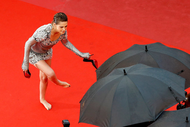 """Jury member Kristen Stewart takes off her shoes as she walk the red carpet for the screening of """"Blackkklansman"""" during the 71st annual Cannes Film Festival at Palais des Festivals on May 14, 2018 in Cannes, France. (Photo by Eric Gaillard/Reuters)"""