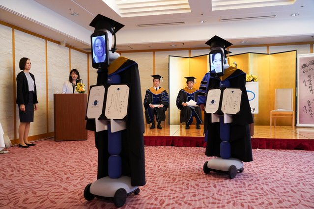 """iPads attached to """"newme"""" robots stand in for graduating students at a ceremony in graduation gowns and hats in Tokyo, Japan on March 28, 2020. (Photo by BBT University/Handout via Rreuters)"""
