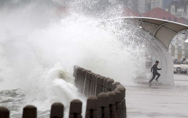A man runs away as waves whipped up by winds surge past a barrier onto a seaside road in Yantai, Shandong Province, China, on May 27, 2013. (Photo by Reuters/Stringer)