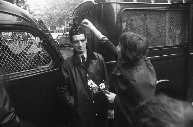 A pacifist student puts a flower in the cap of a wary policeman guarding the Sorbonne during the student riots, Boulevard  Saint-Michel, Paris, France, June 16, 1968. May 1968 gave impetus to the women's liberation movement in France and the recognition of homosexuality. (Photo by Gökşin Sipahioğlu/SIPA Press)