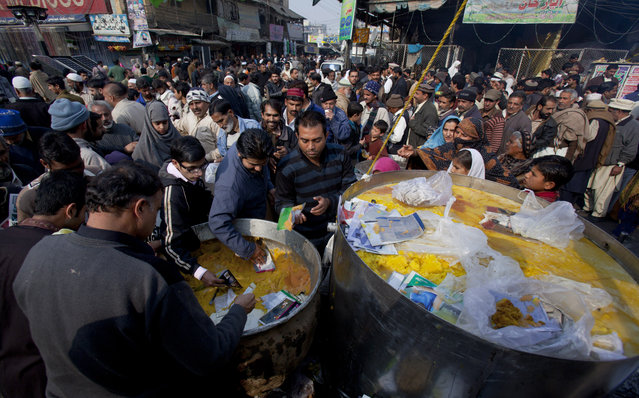 Pakistanis receive free food during a rally marking the birthday of Islam's Prophet Muhammad in Rawalpindi, Pakistan, Sunday, January 4, 2015. Thousands of Pakistani Muslims celebrated by participating in religious ceremonies and distributing free meals among the poor. (Photo by Anjum Naveed/AP Photo)