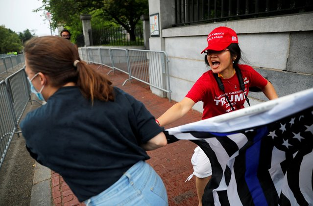 A counter-protester grabs the flag of a pro-police demonstrator during a rally, following weeks of protests against racial inequality in the aftermath of the death in Minneapolis police custody of George Floyd, in Boston, Massachusetts, U.S. June 27, 2020. (Photo by Brian Snyder/Reuters)