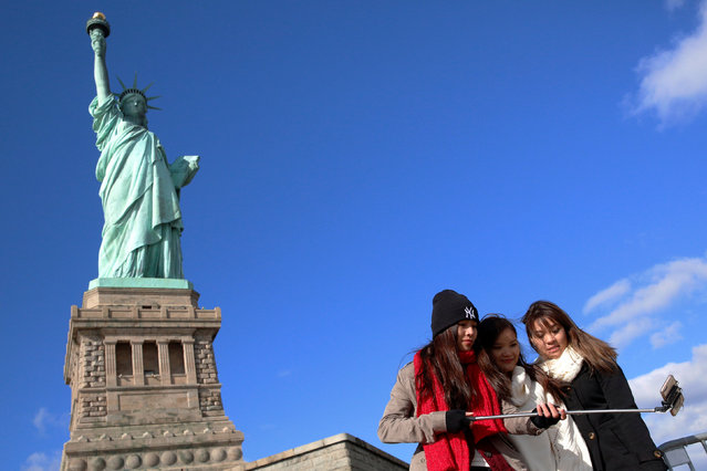 Tourists pose for a selfie in front of The Statue of Liberty on the 130th anniversary of the dedication in New York Harbor, in New York City, U.S., October 28, 2016. (Photo by Brendan McDermid/Reuters)