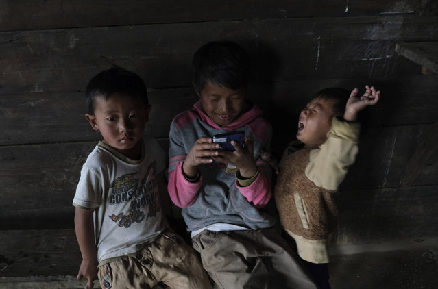 Tangkhul Naga children watch a video on a mobile phone inside their kitchen in Shangshak village, in the northeastern Indian state of Manipur, Tuesday, Jan. 19, 2021. Nagas are in indigenous people inhabiting several northeastern Indian states and across the border in Myanmar. (Photo by Yirmiyan Arthur/AP Photo)