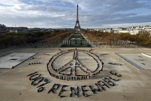 Hundreds of environmentalists arrange their bodies to form a message of hope and peace in front of the Eiffel Tower in Paris, France, December 6, 2015, as the World Climate Change Conference 2015 (COP21) continues at Le Bourget near the French capital. (Photo by Benoit Tessier/Reuters)