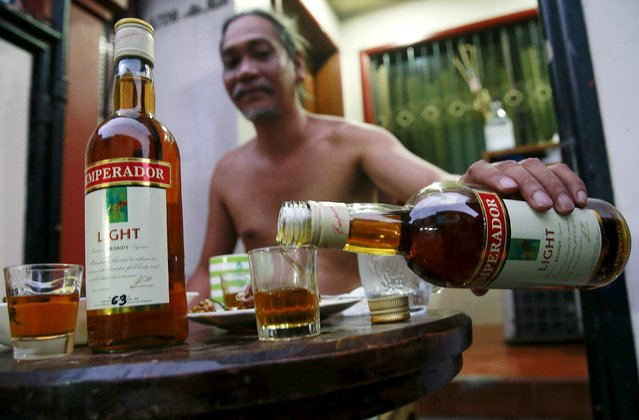 A resident pours a shot of an Emperador brandy inside a house in Manila, Philippines, December 8, 2015. Beam Suntory agreed to sell its Spain-based brandy and sherry business to Emperador of the Philippines for 275 million euros, the companies said on November 30. (Photo by Romeo Ranoco/Reuters)