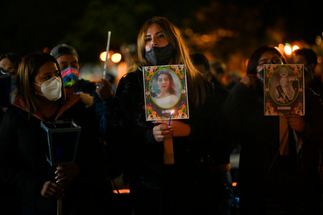 People hold photos during a vigil in memory of women murdered before the International Day of No Violence Against Women at Constitution Square in Guatemala City on November 24, 2020. According to the Guatemalan Women's Group, to date some 444 women have been murdered in 2020. (Photo by Johan Ordonez/AFP Photo)