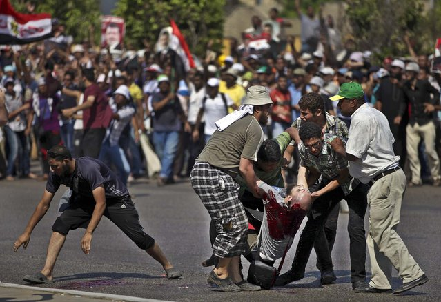 Supporters of ousted Egypt's President Mohammed Morsi pick up the body of a man shot near the Republican Guard building in Cairo, on July 5, 2013. Egyptian troops opened fire on mostly Islamist protesters. (Photo by Khalil Hamra/Associated Press)