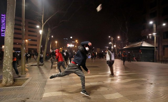 A demonstrator throws an object during a protest in support of Catalan rapper Pablo Hasel, after he was given a jail sentence on charges of glorifying terrorism and insulting royalty in his songs, in Barcelona, Spain, February 19, 2021. (Photo by Albert Gea/Reuters)