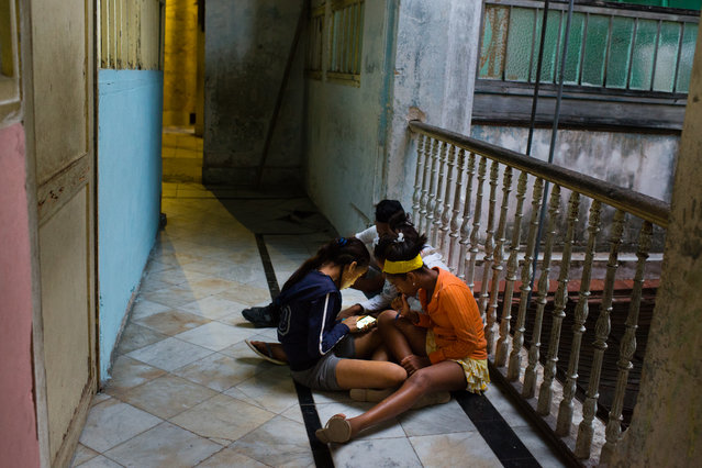 A group of teenagers play on a smart phone in an historic building in Old Havana on January 29, 2015. As talks continue between The United States and Cuba, Cubans could be about to enjoy vastly improved access to communications technology. (Photo by Sarah L. Voisin/The Washington Post)