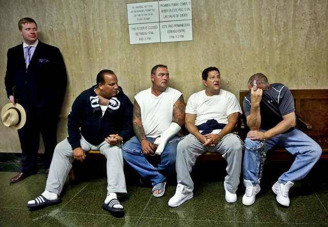 Defendants Anthony Santoro, Anthony Urban, Vito Badano, and Nicholas Bernhard, seated left to right, wait in handcuffs in a courtroom hallway with attorney Timothy Parlatore, for arraignment, in New York, on July 9, 2013. Nine people, members of the infamous Bonanno crime family, have been indicted on enterprise corruption charges. (Photo by Richard Drew/Associated Press)
