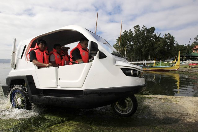 """Engineers drive a gasoline-powered """"Salamander"""", an amphibious tricycle, from the waters of Taal lake to the land during a test drive in Batangas city, south of Manila January 28, 2015. (Photo by Romeo Ranoco/Reuters)"""
