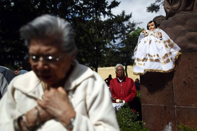 A dressed-up doll representing baby Jesus is seen perched on a wall as people pray nearby during a celebration 40 days after the birth of Jesus in Xochimilco, on the outskirts of Mexico City, February 2, 2015. (Photo by Edgard Garrido/Reuters)