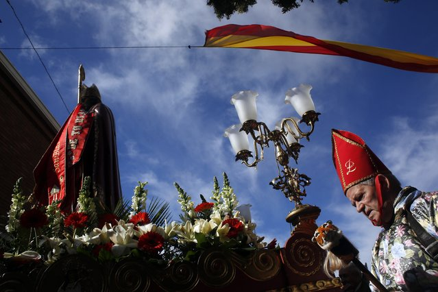 """A believer walks next to the statute of San Blas' (Saint Blaise) during a procession as part of  the """"Endiablada"""" festival in Almonacid del Marquesado, in central Spain February 3, 2015. (Photo by Susana Vera/Reuters)"""