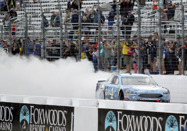 Kevin Harvick smokes his tires down the front stretch after winning a NASCAR Cup Series auto race Sunday, July 22, 2018, at New Hampshire Motor Speedway in Loudon, N.H. (Photo by Mary Schwalm/AP Photo)