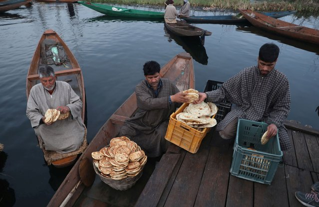 A roadside vendor sells the local bread to Kashmiri boatmen on the interior of Dal Lake in Srinagar, Kashmir, India, 10 March 2021. Kashmiri boatmen work to earn their livelihood mostly by selling vegetables produced in the lake, ferrying tourists, and cleaning the lake of weeds while women are often seen selling the fish caught by their men. (Photo by Farooq Khan/EPA/EFE)