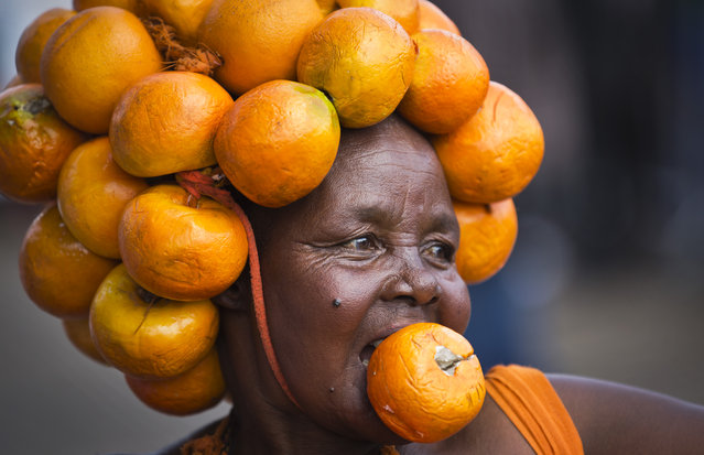 A supporter of Kenyan opposition leader Raila Odinga's Orange Democratic Movement (ODM) party wears a head-dress made of oranges, the party's color, as she attends a rally to welcome Odinga back to the country, in downtown Nairobi, Kenya Saturday, May 31, 2014. (Photo by Ben Curtis/AP Photo)