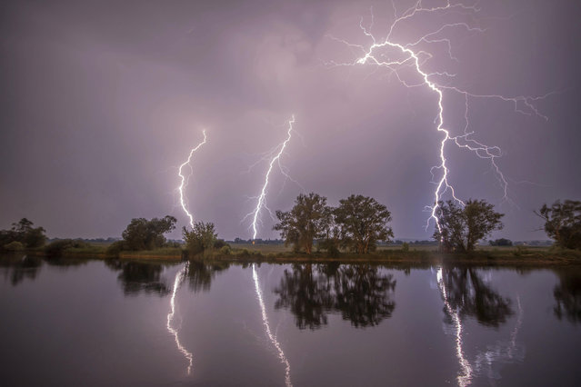 In this May 27, 2018 photo thunderbolts are reflected near Premnitz, eastern Germany. (Photo by Julian Staehle/DPA via AP)