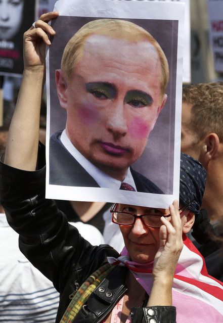 "An activist holding a placard depicting Russian President Vladimir Putin participates at a protest against Russia's new law on gays, in central London, Saturday, August 10, 2013. Hundreds of protesters, called for the Winter 2014 Olympic Games to be taken away from Sochi, Russia, because of a new Russian law that bans ""propaganda of nontraditional sexual relations"" and imposes fines on those holding gay pride rallies. (Photo by Lefteris Pitarakis/AP Photo)"