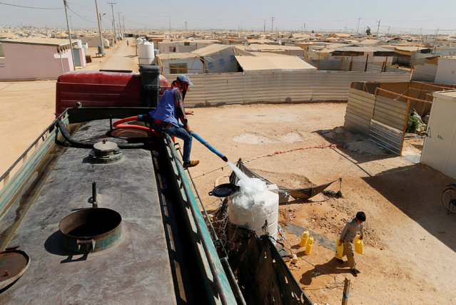 A Syrian man sits on a portable tank as he fills a container with water in Zaatari refugee camp near the border with Syria, in Mafraq, Jordan October 14, 2016. (Photo by Ammar Awad/Reuters)