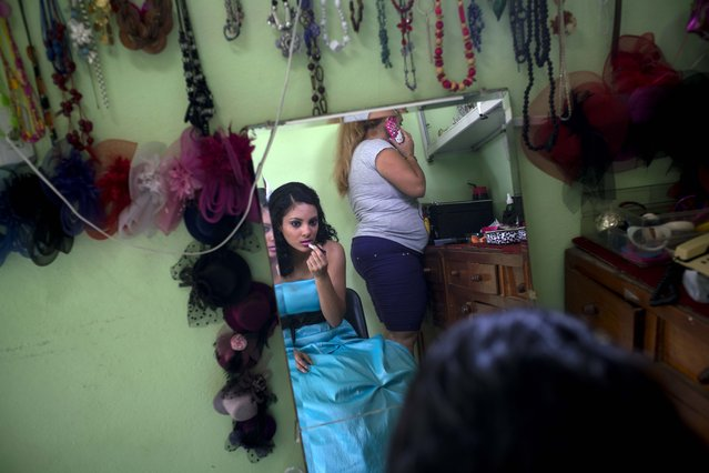 In this December 18, 2015 photo, Daniela Santos Torres, 14, applies lipstick as she gets ready for a portrait session with EstudioMayer which her family hired to take her quinceanera photos and organize her birthday party in Havana, Cuba. (Photo by Ramon Espinosa/AP Photo)