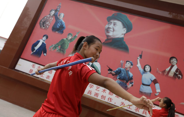 A student from an art school practices next to a poster with a portrait of the late Chairman Mao Zedong in Nanjie village of Luohe city in China's central Henan province, September 24, 2012. (Photo by Jason Lee/Reuters)