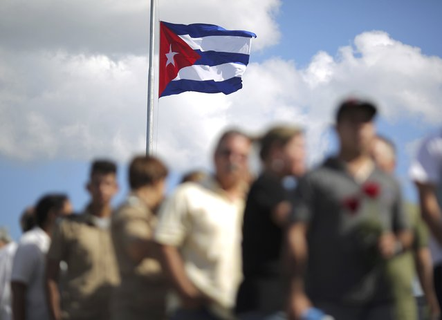 A Cuban flag flies overhead as people wait in line to pay tribute to Cuba's late President Fidel Castro in Havana, Cuba, November 28, 2016. (Photo by Carlos Barria/Reuters)
