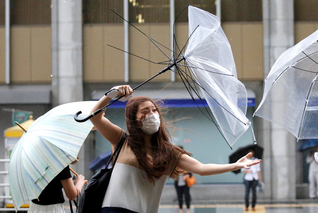 A woman using an umbrella struggles against a heavy rain and wind as Typhoon Shanshan approaches Japan's mainland in Tokyo, Japan August 8, 2018. (Photo by Toru Hanai/Reuters)