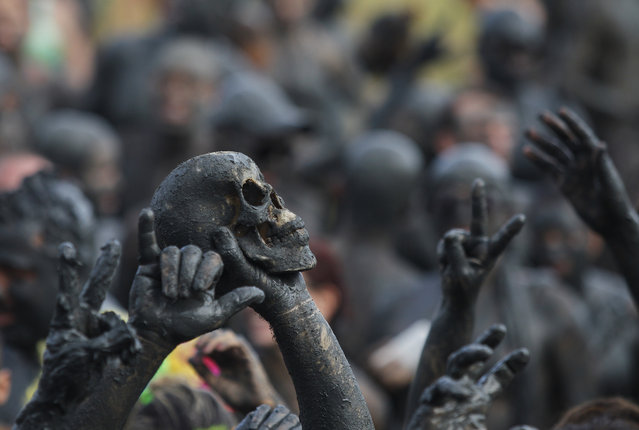 "A man holds up a skull during the traditional ""Bloco da Lama"" or ""Mud Block"" carnival party, in Paraty, Brazil, Saturday, February 14, 2015. (Photo by Leo Correa/AP Photo)"