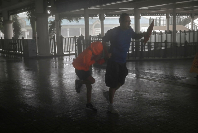 A man and a girl walk against strong winds from Typhoon Mangkhut on a pier on Victoria Habour Hong Kong, Sunday, September 16, 2018. (Photo by Vincent Yu/AP Photo)