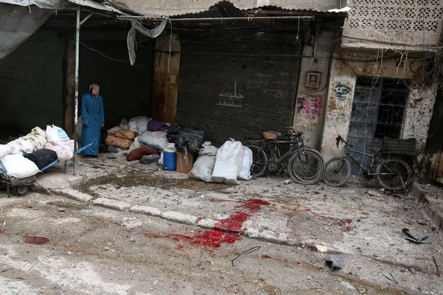 A woman stands near the blood stained ground after strikes on rebel-held besieged al-Zebdieh district, in Aleppo Syria December 5, 2016. (Photo by Abdalrhman Ismail/Reuters)