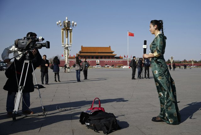 A journalist reports outside the Great Hall of the People during the opening session of the Chinese People's Political Consultative Conference (CPPCC), at Tiananmen Square in Beijing, March 3, 2015.  REUTERS/Kim Kyung-Hoon