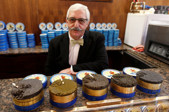 Armen Petrossian, CEO of Petrossian, son of the brand's Armenian founder and one of the world's oldest and largest caviar specialists, poses with tin cans of caviar inside his shop in Paris, France, December 13, 2016. (Photo by Charles Platiau/Reuters)