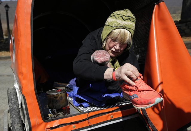 "Sixty-eight year old cross-country runner Rosie Swale-Pope removes her running shoes while in her cart, ""The Icebird"", in Upperville, Virginia March 13, 2015. (Photo by Gary Cameron/Reuters)"