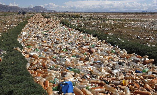 Plastic bottles and garbage float on the Tagaret River, which flows into Uru Uru Lake, near Oruro, Bolivia, Thursday, March 25, 2021. (Photo by Juan Karita/AP Photo)