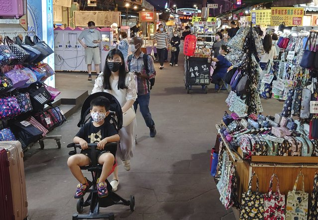 People wear face masks to protect against the spread of the coronavirus at a night market in Taipei, Taiwan, Friday, May 14, 2021. (Photo by Chiang Ying-ying/AP Photo)