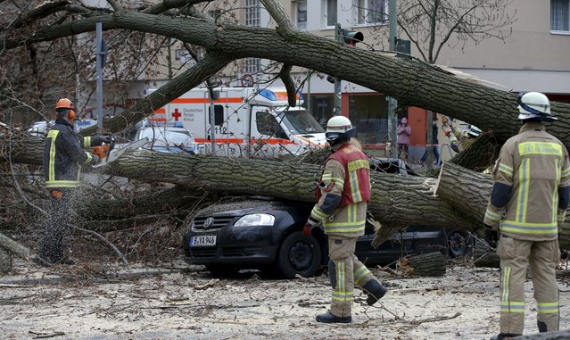 Firefighters remove parts of a tree from a street at Wedding district as Storm Niklas strikes in Berlin March 31, 2015. One of the strongest storm fronts in years hit Germany on Tuesday, as Storm Niklas uncovered roofs, toppled scaffolding and caused severe disruption to rail services. (Photo by Fabrizio Bensch/Reuters)