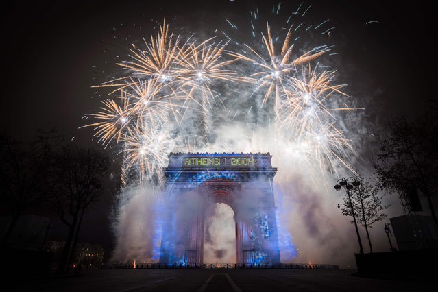 Fireworks explode over the Arc de Triomphe monument illuminayed by a laser and 3D mapping display on the theme of the Paris 2024 bid for the Olympic Games, as part of New Year celebrations on January 1, 2017 in Paris. (Photo by Lionel Bonaventure/AFP Photo)
