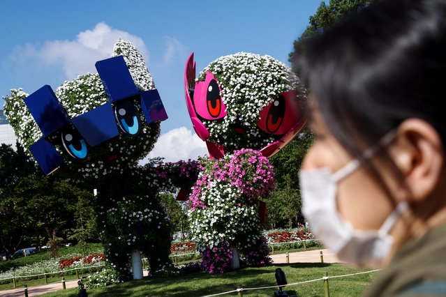 A woman stands in front of the Tokyo 2020 Olympic and Paralympic mascots Miraitowa and Someity as the coronavirus disease (COVID-19) pandemic continues in Tokyo, Japan, July 17, 2021. (Photo by Thomas Peter/Reuters)