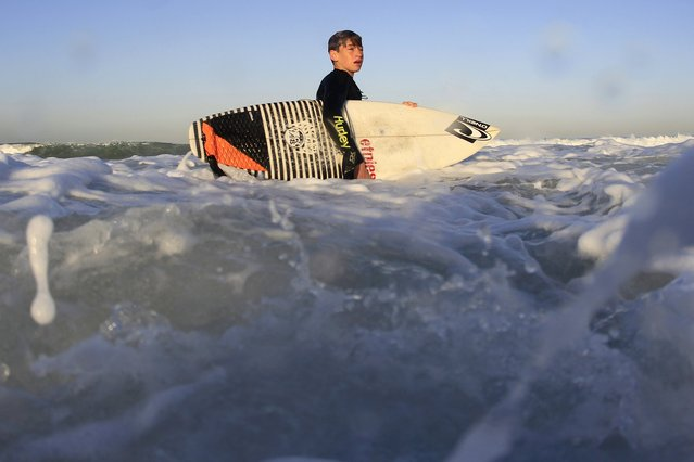 Luke Personius, 12, wades through surf before school at sunrise in Hermosa Beach, California April 2, 2015. (Photo by Lucy Nicholson/Reuters)