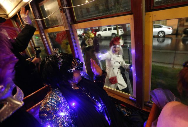 """Members of the """"Societe des Champs Elysee"""" ride the Rampart-St. Claude street car line, which just opened last fall, to commemorate the official start of Mardi Gras season, in New Orleans, Friday, January 6, 2017. (Photo by Gerald Herbert/AP Photo)"""