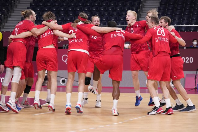Denmark's team players celebrate as they won the men's semifinal handball match between Spain and Denmark at the 2020 Summer Olympics, Thursday, August 5, 2021, in Tokyo, Japan. (Photo by Pavel Golovkin/AP Photo)
