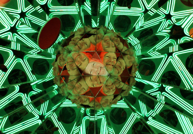 Local artist Tom Chouteau looks through the Hands In Scope kaleidoscope which is part of his Kaleidoscopia display at the German American Heritage Center in Davenport, Iowa, Wednesday, February 11, 2015. (Photo by Kevin E. Schmidt/AP Photo/The Quad City Times)