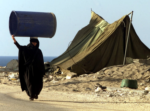 A Palestinian refugee woman carries a water container on her head in the Khan Younis refugee camp near the Kefar Yam Jewish settlement on in the Gaza strip, November 2001. (Photo by Desmond Boylan/Reuters)
